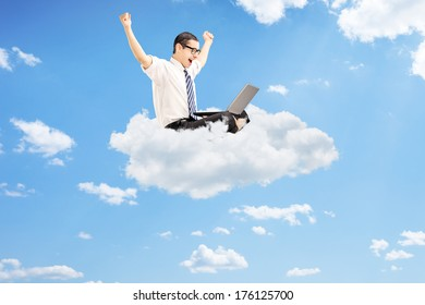 Young businessman working on a laptop and gesturing happiness seated on cloud with blue sky in the background