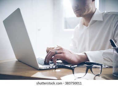 Young businessman working on laptop at his office, close up of man lawyer sitting in office interior and using computer