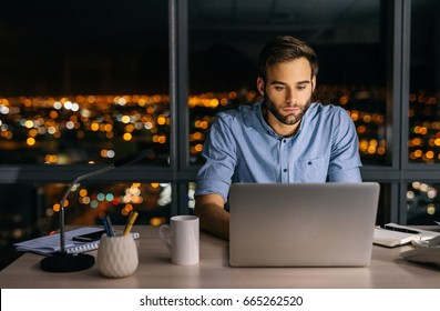 Young businessman working on a laptop at his office desk late into the night in front of windows overlooking the city