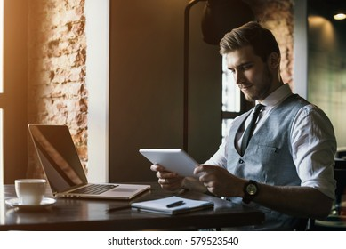 Young businessman working on a plan of Internet project on the laptop. Man discusses business matters by phone. Working computer for internet research. Digital marketing. Development