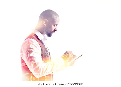 Young businessman working on a tablet pc double exposure side view