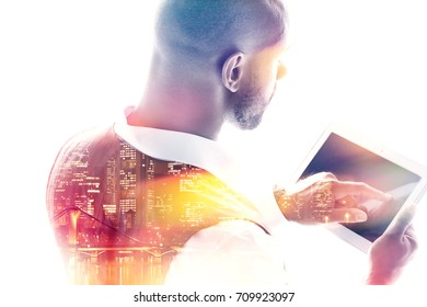 Young businessman working on a tablet pc rear view double exposure