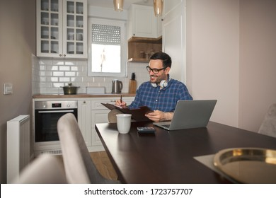 Young businessman working remotely holding pen making notes in his notebook while sitting in front laptop and wearing headphones around his neck.