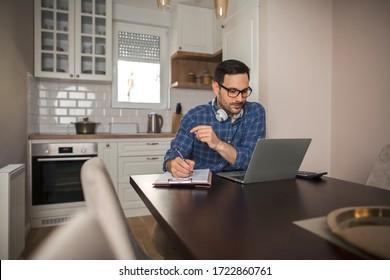 Junge Geschäftsleute, die ferngesteuert mit Laptop arbeiten, während sie einen Stift halten und Notizen in seinem Notizbuch schreiben.