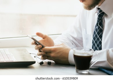Young businessman working,  with smartphone in cafe