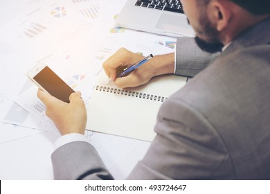 Young businessman is working, using smart phone, laptop computer and writing on his notebook