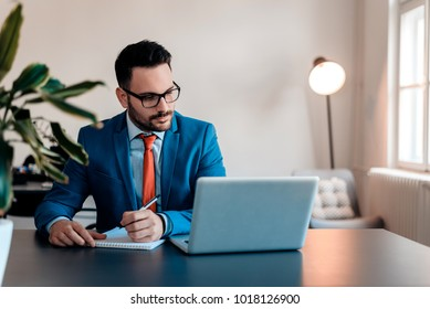 Young businessman working writing notes sitting in a desktop at office.