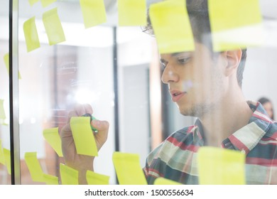 Young businessman writing on sticky notes in office