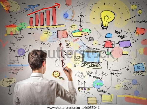 junger Geschäftsmann, der an die Wand schreibt