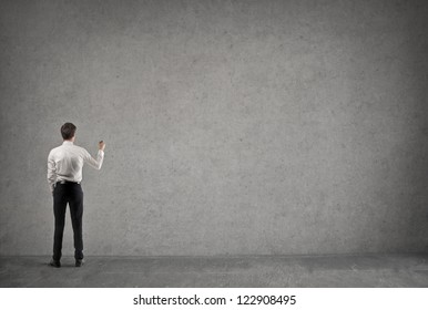 Young businessman writing something on a large empty wall