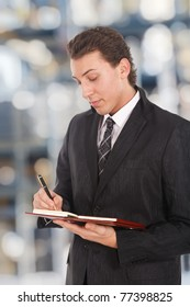 Young businessman writing something on his agenda. Blurred background.
