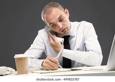 Young businessman writing something while making  a call
