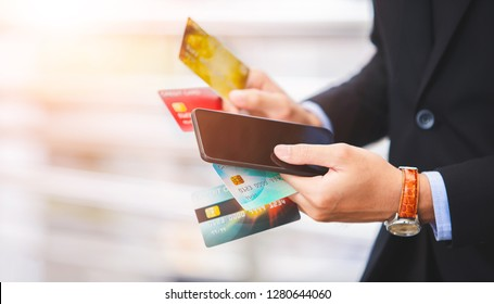 Young businessman's hand using mobile phone to calculating his expenses and debt from many credit cards. Credit card debt concept.