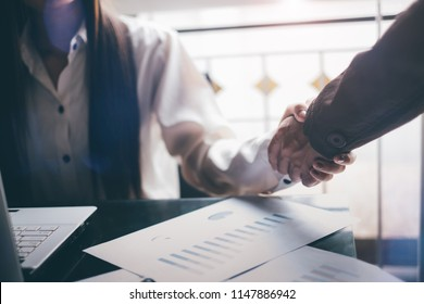 Young businessmen analyze graphs to meet goals set over blurred Business graph on the table in office .Film tones and Light fair. select focus