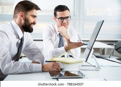 Young businessmen discussing new project at office