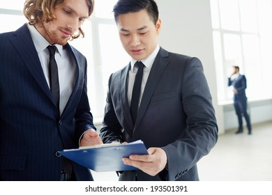 Young businessmen discussing plan or paper at meeting in office