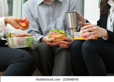 Young businessmen eating homemade lunch during break