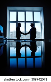 Young businessmen greeting one another by handshake