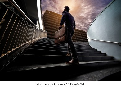 Young businessmen have power of ambition to work on the morning. He confidently stepped up the stairs. In his hand holding a business leather bag.