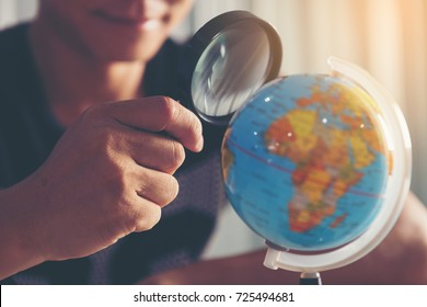 Young businessmen are looking through a magnifying glass to the globe to find a target audience. Look for or find a business target (concept)