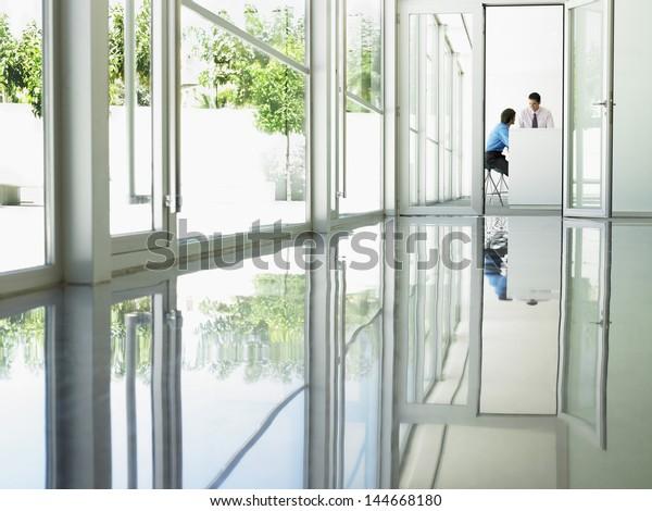 Young businessmen in meeting viewed through open office door