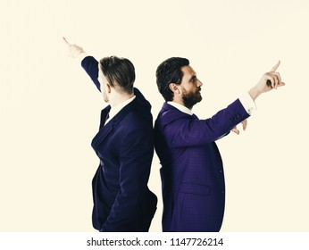 Young businessmen pointing in two different directions at same time. Handsome guys nice suits on white background, isolated.