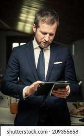Young businessmen using PC tablet at home before breakfast