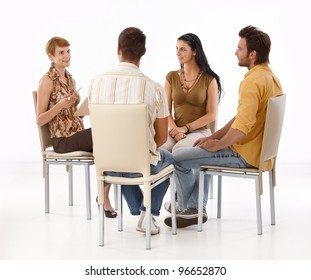 Young businesspeople brainstorming, sitting in circle.?