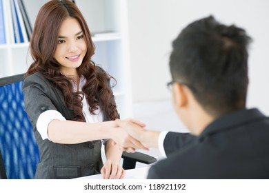 Young businesspeople concluding a deal and sealing it with a handshake