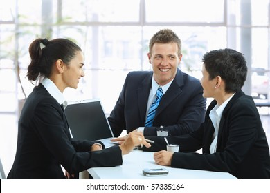 Young businesspeople having a business meeting at coffee table in office lobby, using laptop computer. Copyspace on blank screen.