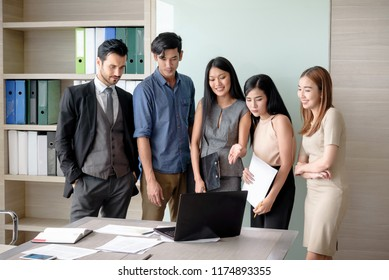 young businesspeople, man and woman, look at laptop for business project in the meeting