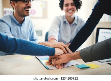 Young businesspeople sitting around table in a modern office, stacking hands.