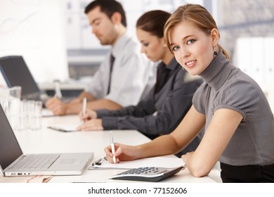 Young businesspeople sitting at meeting table in office, having business training, writing notes.?
