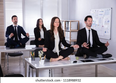 Young Businesspeople Sitting On Desk Meditating In Office