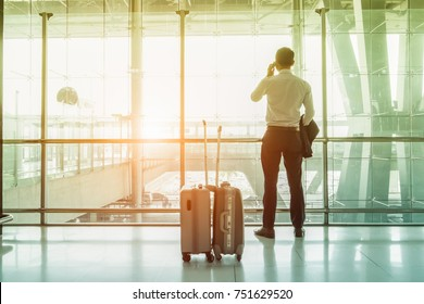 Young businesspeople stand at the airport during sunset and are talking on the phone to inform them of their important business travel overseas.