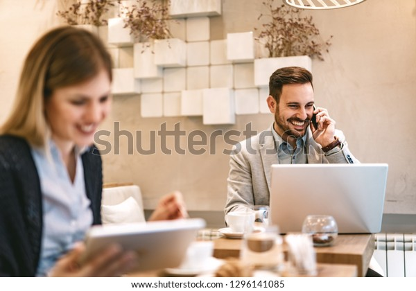 Young businesspeople surfing the internet on a break in a cafe. Happiness man working at laptop and using smarthphone. Smiling woman using digital tablet and drinking coffee.