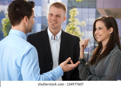 Young businesspeople talking in break time outside of office building, smiling, gesturing.