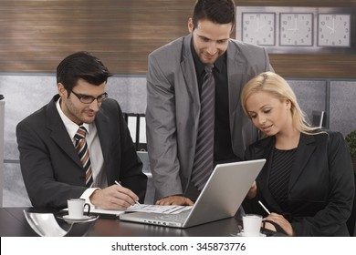 Young businesspeople working together in meetingroom, using laptop computer.
