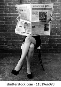 Young businesswoman against brick wall reads Financial Times newspaper with financial and business news. July 2018, United Kingdom