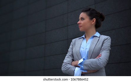 Young Businesswoman against grey building facade with copy space
