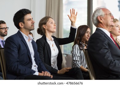 Young businesswoman from audience raising hand to ask question