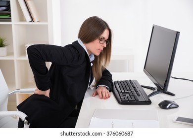 Young Businesswoman With Backpain Sitting On Chair At Workplace