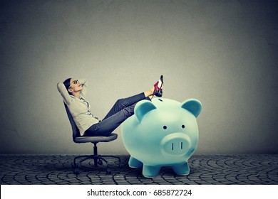 young businesswoman with big piggy bank relaxing sitting on chair