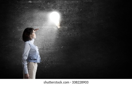 Young businesswoman blinded with light going from bulb
