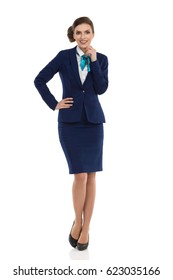 Young businesswoman in blue formalwear and high heels is posing with hand on hip and looking at camera. Front view. Full length studio shot isolated on white.