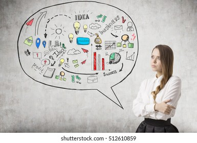 Young businesswoman with braided hair is standing near concrete wall with speech bubble and business sketch in it. Concept of business idea