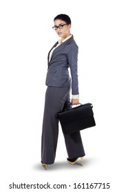 Young businesswoman with briefcase standing on white background