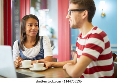 Young businesswoman and businessman in casualwear spending coffee-break in cafe