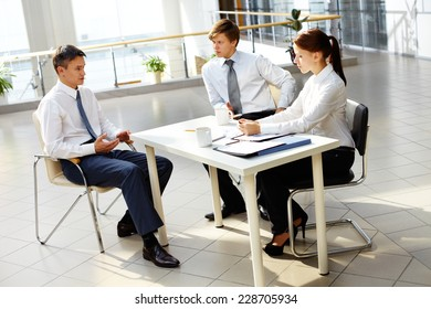Young businesswoman and businessman looking at their boss explanations at meeting