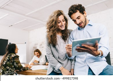 Young businesswoman and businessman working in office with tablet